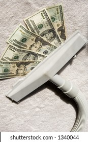 Attachment to vacuum cleaner sucking up five $20 bills on sunlit white carpet
