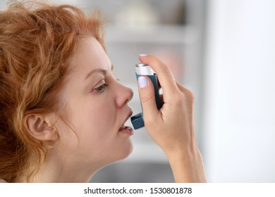 Attack from asthma. Close up of sick woman using inhalator while having attack from asthma