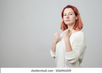 Attack position of confident woman being ready to fight looking on her offender. Boxer girl going to punch with strength training at sport club over gray background. Behaviour, sport