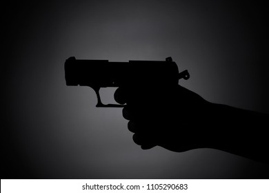 attacking with a gun -shadow in the dark