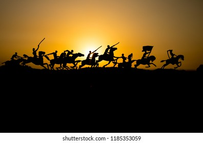 Attacking scene. War concept. Riders on horse ready to fight and soldiers on a dark foggy toned sunset background. Battle scene battlefield of fighting soldiers. Selective focus