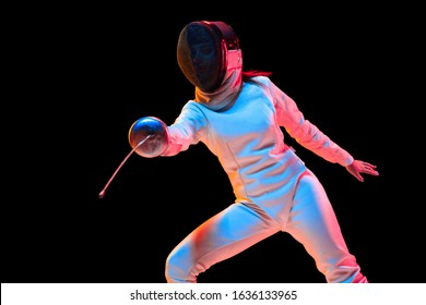Attacking. Teen girl in fencing costume with sword in hand isolated on black background, neon light. Young model practicing and training in motion, action. Copyspace. Sport, youth, healthy lifestyle.