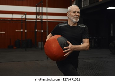 Attactive sporty senior man enjoying phycisal exercise at fitness center. Unshaven elderly retired male in sports clothes training in gym, holding weight medicine ball, doing upper body workout