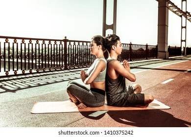 Attaining mindfulness. Two young people doing a relaxation exercise being outside on a clear sunny day