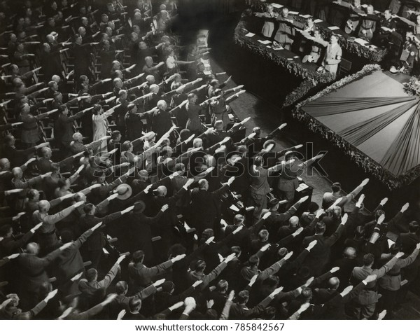 Attendees give Hitler the Nazi salute during the nation anthem, Oct. 9, 1935. They were meeting at the Kroll Opera in Berlin, to organize the Winter Relief festive to help finance charitable work