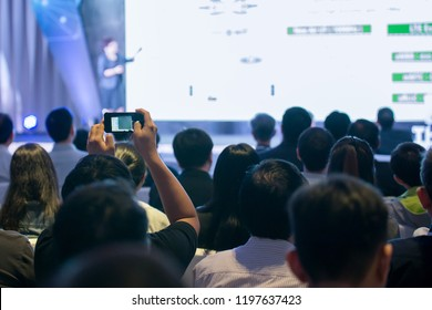 Attendees use smartphone photography in the seminar room