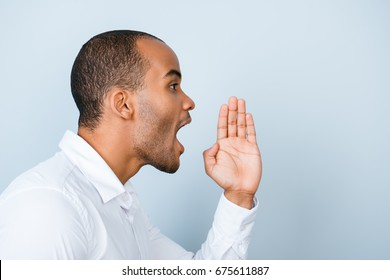 Attention! Cheerful young  american mulatto man in white formal shirt is shouting and holding hand near her open mouth on light grey background