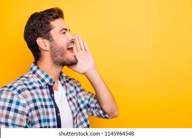¡Atención! Un retrato de cerca de с jovencito brunet en pantalones a cuadros está sosteniendo la mano cerca de su boca abierta aislada en un fondo amarillo vívido con espacio para texto