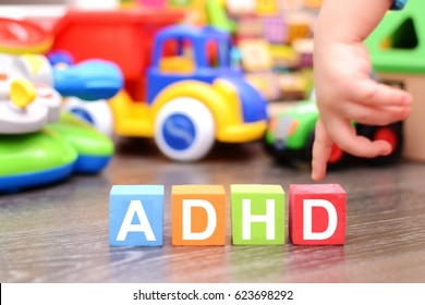 Attention Deficit Hyperactivity Disorder or ADHD concept with toddler hand touching colored cubes against toys