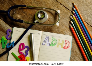 Attention Deficit Hyperactivity Disorder or ADHD concept. Top view of stethoscope,wooden numbers,colorful pencils and notebook written with ADHD on wooden background.