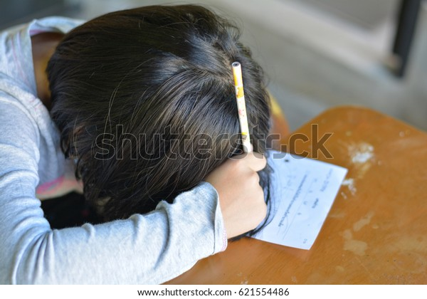 Attention deficit hyperactivity disorder (ADHD) and Learning disability (LD) in children and teens concept.Female cute child asleep on paper.Asian students sleeping while practice math subject at home