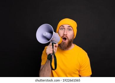 Attention! European man shouting in megaphone on black background