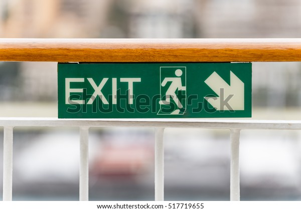 Attention green Exit sign with arrow on wooden railing cruise sh.  Green Exit sign with arrow pointing to the right showing the direction and a running man icon for emergencies