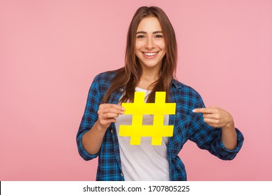 Attention to interesting blog post. Happy girl in shirt pointing at yellow hashtag symbol, making important topic popular, setting trends on Internet. indoor studio shot isolated on pink background