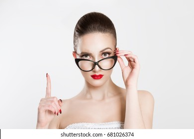 Attention listen to me. Close up portrait young woman wagging her finger holding glasses skeptically isolated white grey wall background. Negative human emotion face expression body language attitude