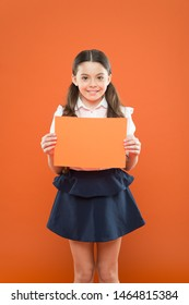 attention please. school girl hold paper on orange background. copy space. happy little girl in school uniform with add. useful information. back to school. look here. writing notes. modern education.