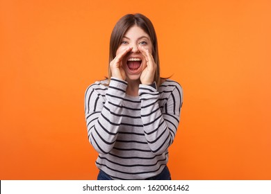 Attention! Portrait of stressed furious young woman with brown hair in long sleeve shirt standing, holding arms near wide open mouth and screaming. indoor studio shot isolated on orange background