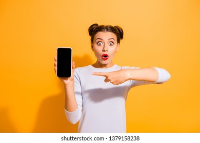 Attention sales discounts! Portrait of astonished person impressed by incredible news information from social network pointing at mobile phone isolated over colorful background in white jumper