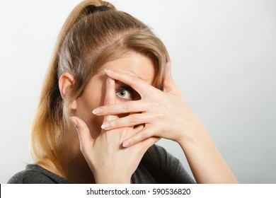 Attention shame observation psychology disorder concept. Shy girl hiding her face. Young blonde curious lady looking through her fingers while covering rest of head.