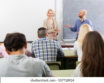 Attentive adult students with positive female teacher at training session for employees