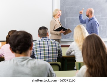 Attentive adult students with smiling female teacher at training session for employees
