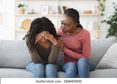Attentive african american lady comforting her upset crying girlfriend or sister, giving her hug, saying supportive words, living room interior, copy space. Support in friendship concept