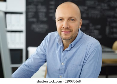 Attentive balding middle-aged businessman sitting at his desk looking at the camera with an intent expression and quiet smile