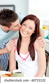 Attentive boyfriend kissing his girlfriend at her cheek during breakfast in the kitchen at home