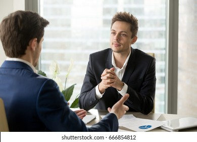 Attentive businessman listening to business partner talking during negotiations, thinking over his ideas, business team discussing project, financial adviser consulting client at meeting in office
