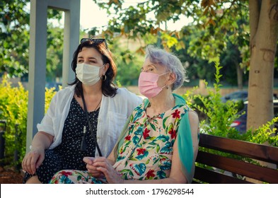 Attentive caregiver or companion and a senior adult woman in protective masks are sitting on a park bench. Summer sunny day.