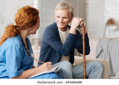Attentive delicate therapist talking to her elderly patient