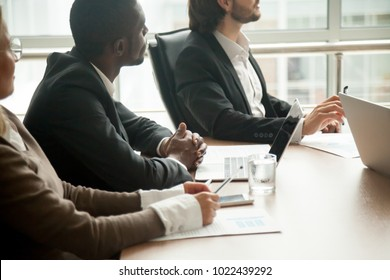 Attentive diverse businesspeople sitting at conference table focused on listening at meeting, multiracial corporate team training, partners group at negotiations or business seminar concept, close up