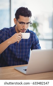 Attentive executive having coffee while using laptop at desk in office