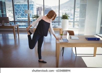Attentive executive using laptop while exercising in office