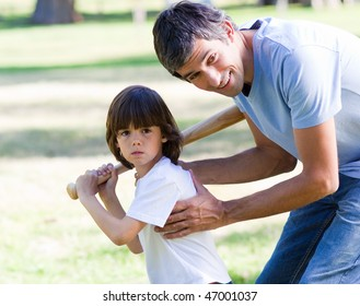 Attentive father playing baseball with his son in the park