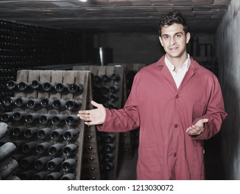 Attentive glad  friendly man winery employee wearing coat working in aging section with bottle racks in cellar