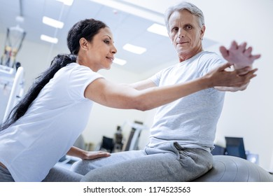 Attentive glance. Serious calm aged man feeling concentrated while sitting on a big fitball in a rehabilitation center and looking at his hand while a cheerful experienced doctor helping him