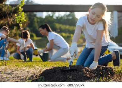 Attentive kid using rake for planting