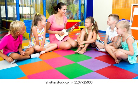 Attentive kids sitting around cheerful teacher with small guitar and listening to music in class