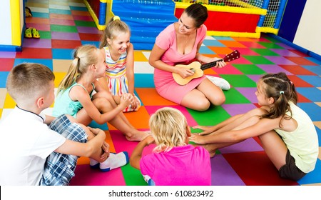 Attentive kids sitting around young beautiful teacher with small guitar and listening to music in class