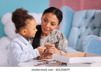 Attentive kind mom giving her child a puzzle piece