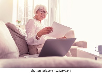 Attentive lady investigating. Attentive grey-haired lady investigating documents and working with laptop at home