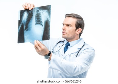 Attentive male doctor practitioner with stethoscope looking at x-ray image isolated on white