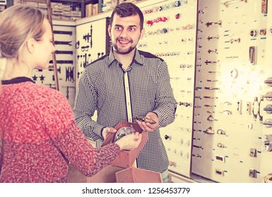 attentive male seller assisting woman in choosing door handles in houseware shop