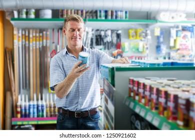 attentive man customer choosing paint bucket in housewares hypermarket