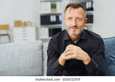 Attentive man gazing at the camera with his hands clasped in front of him as he relaxes on a couch at home