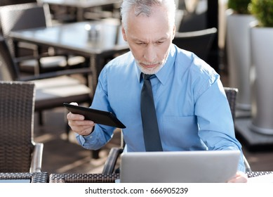 Attentive man using hid gadgets while preparation