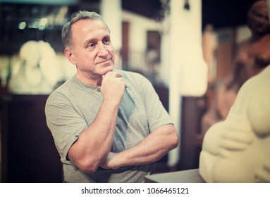 attentive middle aged man examining exposition in museum hall of ancient sculpture