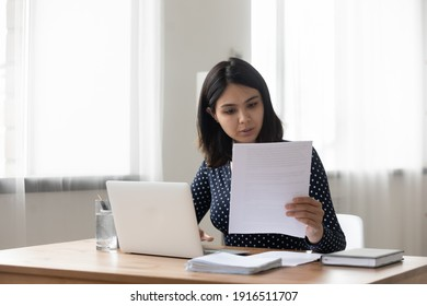 Attentive millennial asian female holding paper letter document reading financial statement. Focused vietnamese business woman worker employee review offer proposal study job contract terms conditions