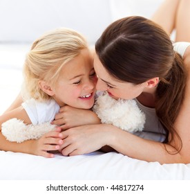Attentive mother hugging her daughter lying on a bed
